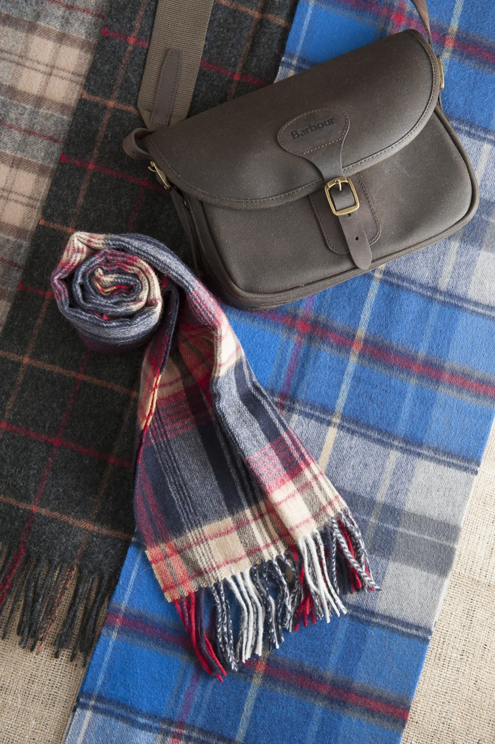 Barbour waxed cartridge bag, £79.95, Barbour lambswool tartan scarves (left, middle and rolled), from £24.95, The Golden Fleece, Rye 01797 224271 www.thegoldenfleece.co.uk; Joules scarf (right), £19.95, Charity Farm Countrystore, Cranbrook 01580 713189 www.charityfarmcountrystore.co.uk
