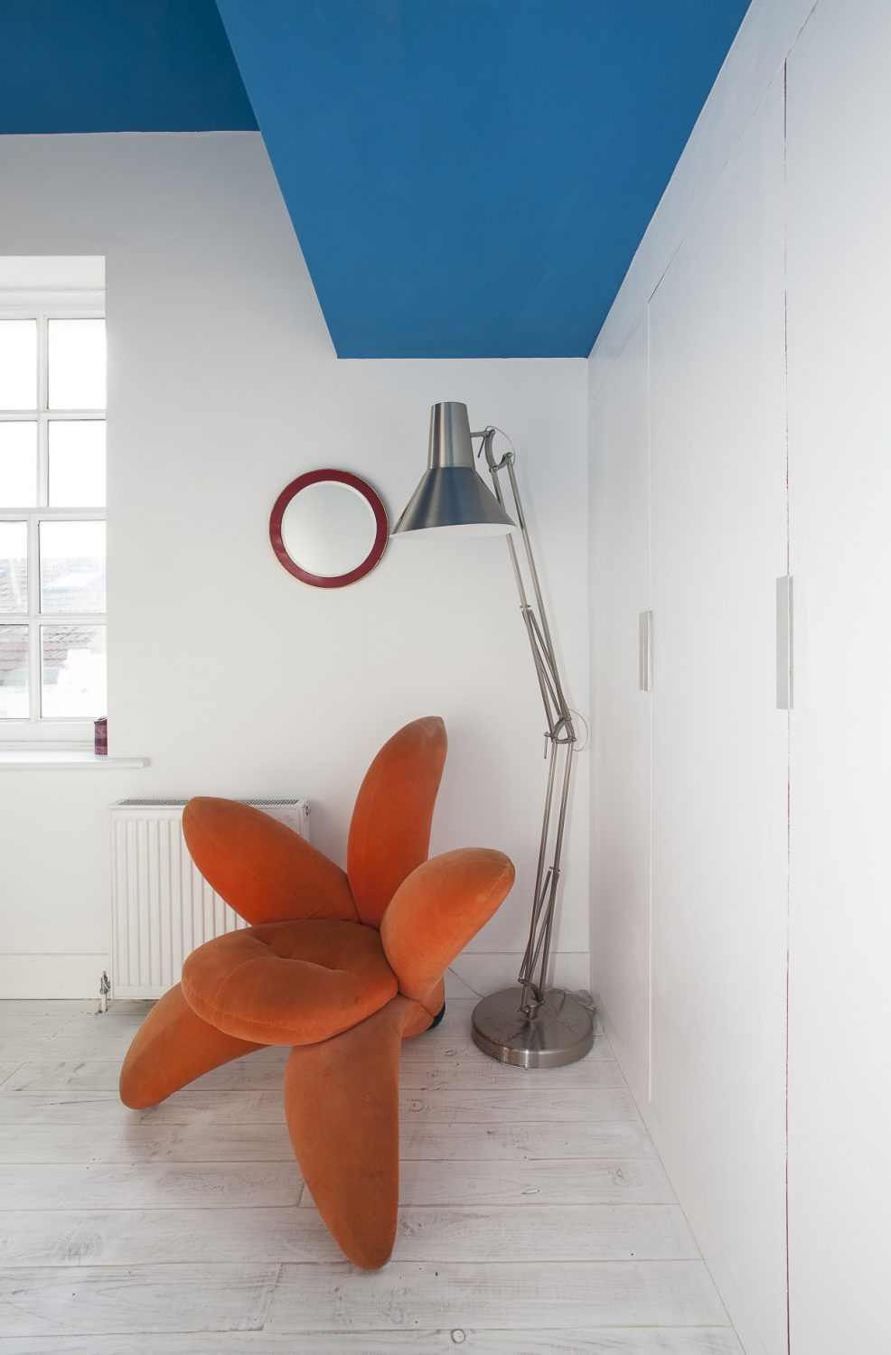 A second guest bedroom is home to a vibrant upholstered lily chair by Japanese designer Masanori Umeda