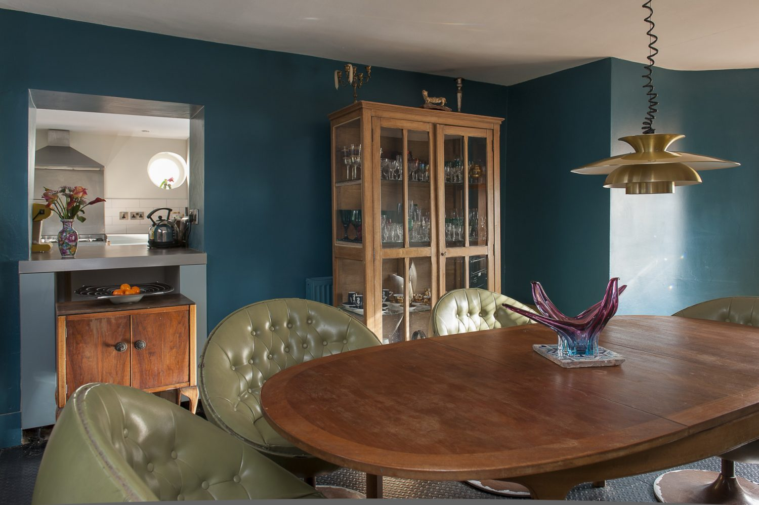 Nadene found the oval 60s teak dining table in a local charity shop and the couple have surrounded it with deep, green leather nightclub swivel chairs from eBay. A French glass-fronted and sided linen cabinet displays Nadene's eclectic collection of glassware