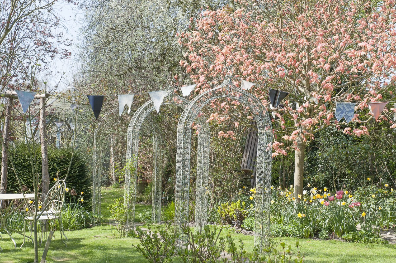 The pretty cottage garden, strung with reams of fabric bunting, has burst into life with an explosion of greens, pinks, reds and yellows