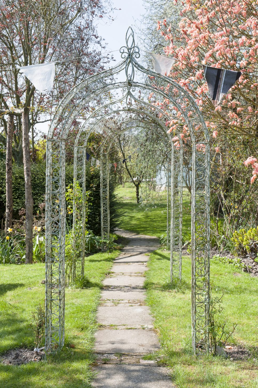 A terraced arbor and a paved path, flanked by daffodils, hydrangeas and tulips, lead down to a summerhouse and chicken coop – home to