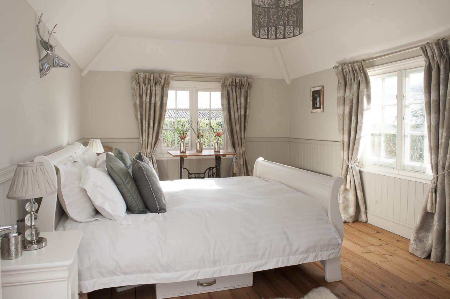 The sleigh bed was bare wood but has been painted white by Charlotte and the dressing table next to it is the base of an old Singer sewing machine