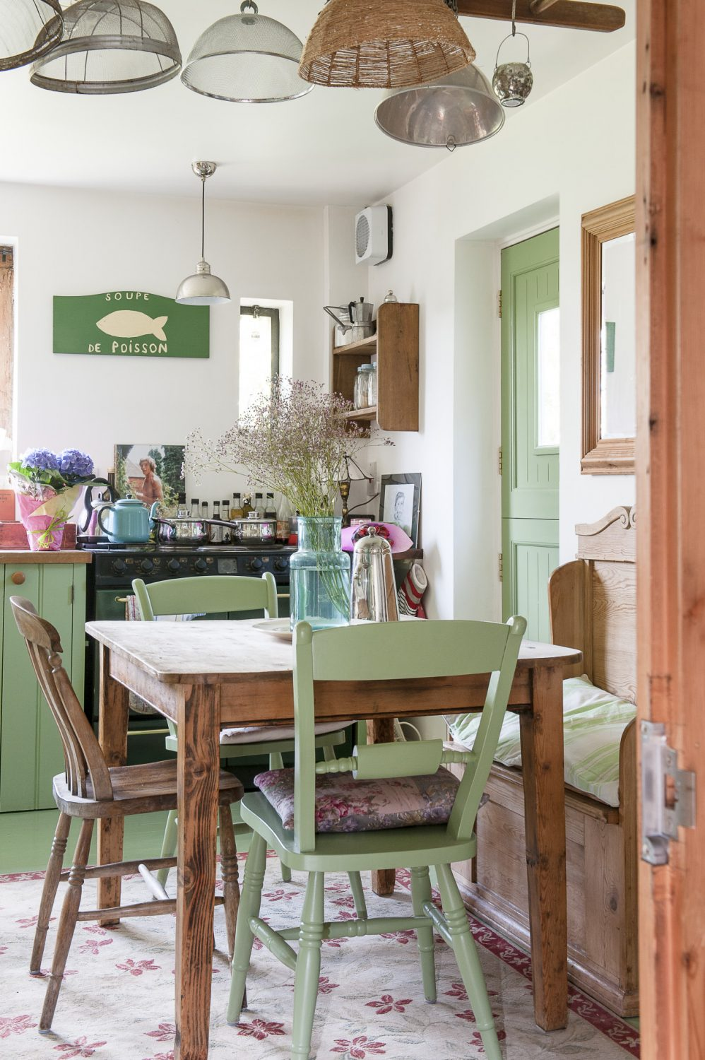 In the kitchen sieves and colanders hang from an old wooden orchard ladder suspended horizontally from the ceiling above the stripped pine dining table