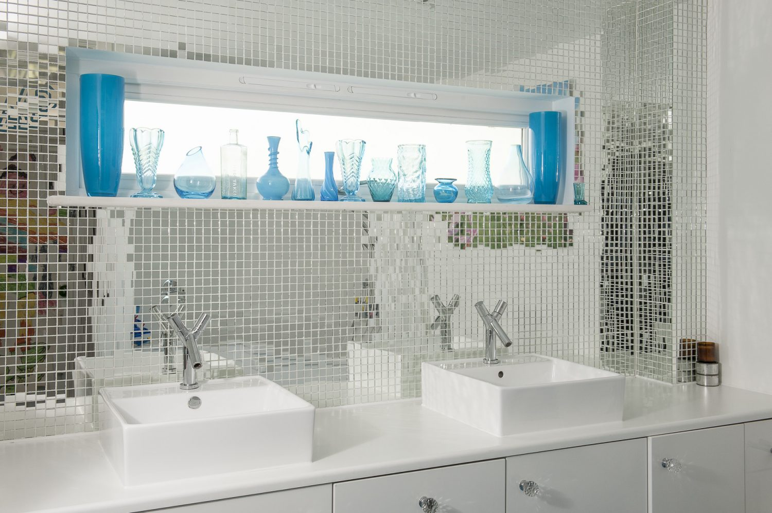 Like the downstairs loo, the rear wall of the family bathroom is tiled with mirrored mosaics