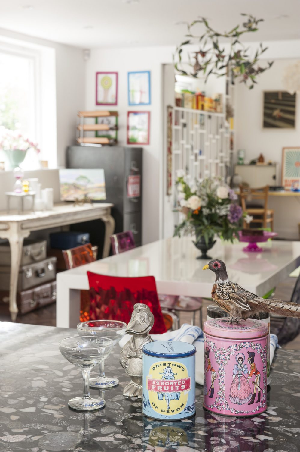 A selection of well-preserved vintage sweet and tea tins, a Donald Duck money box and Babycham glasses from the shop are grouped together on the kitchen counter