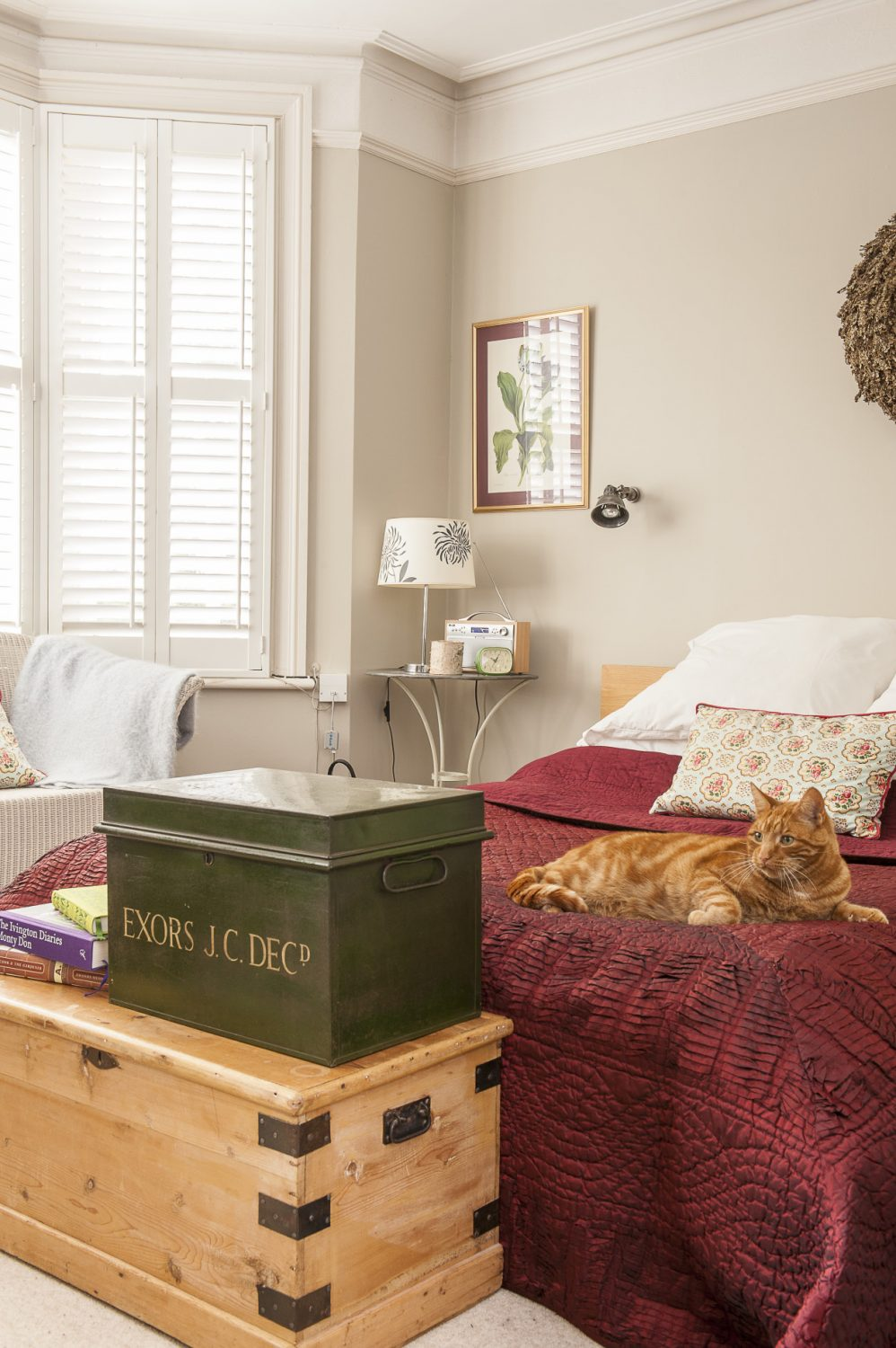 At the foot of the bed is a pine chest and an old steel deed box