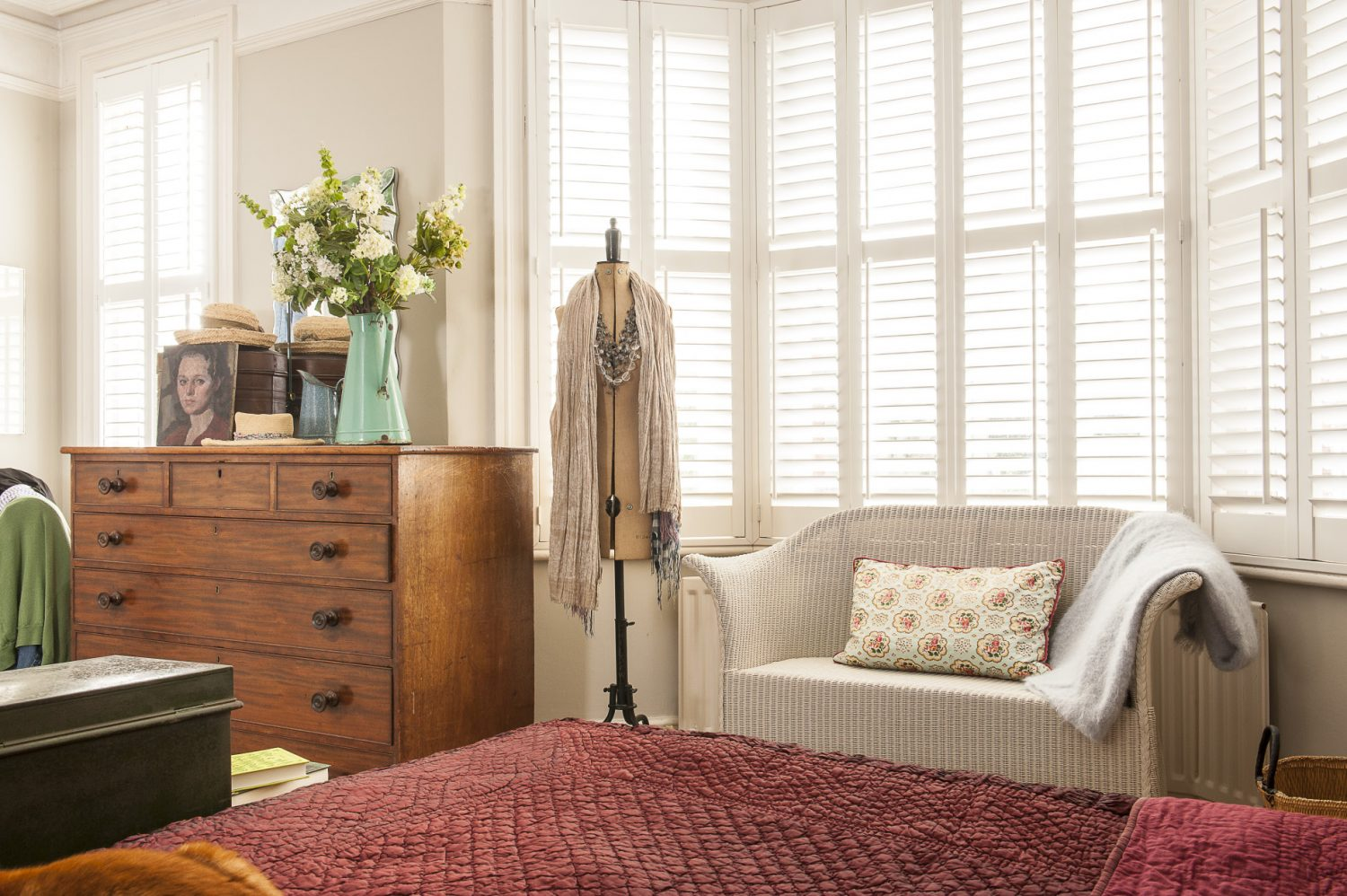 The master bedroom features a superb period chest of drawers in glowing oak that Diana picked up for £75 at Lots Road auction. Behind it in the window is a Victorian tailor's dummy hung with a silk scarf and a blizzard of beads