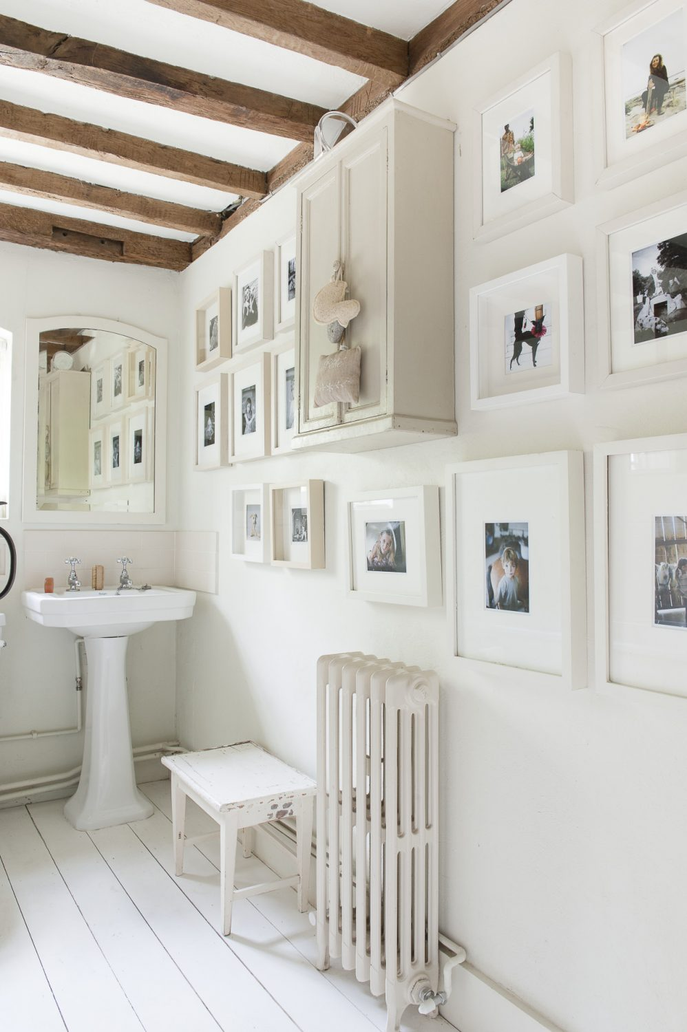 Family photographs cover the walls of the pure white bathroom