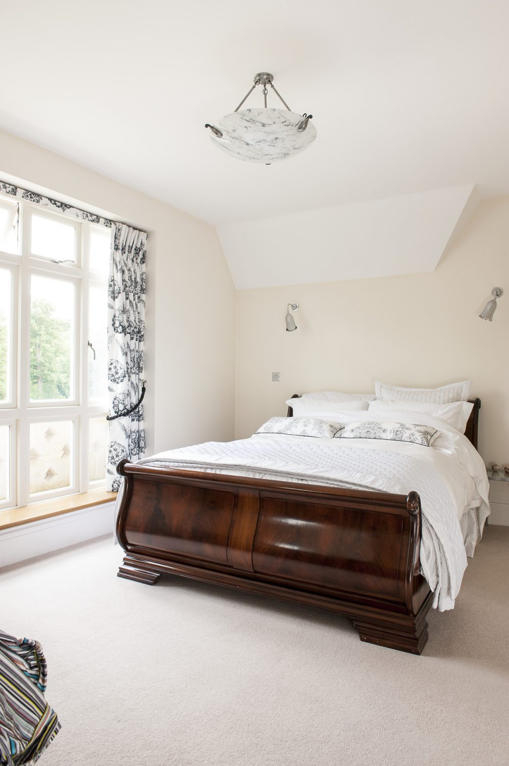 The master bedroom and en suite bathroom are simply decorated and furnished with an elegantly dramatic black and white colour scheme