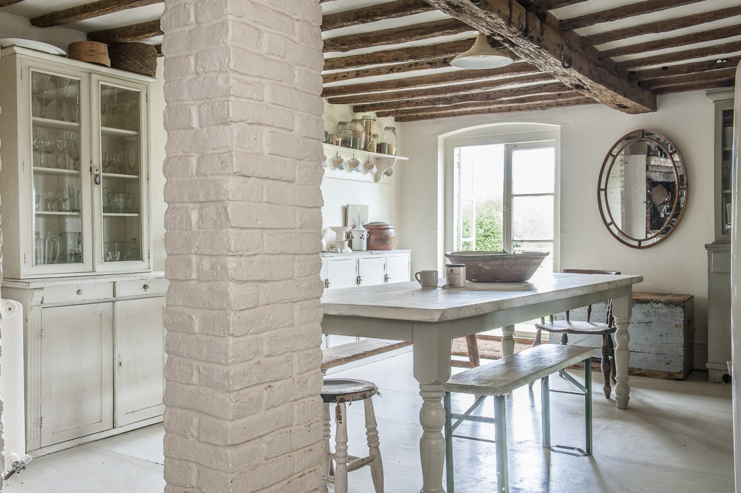 The largest single room in the house is the kitchen that runs the full width of the property. It's a glorious room of white-on-white with warmth provided by glowing timbers and bare brick