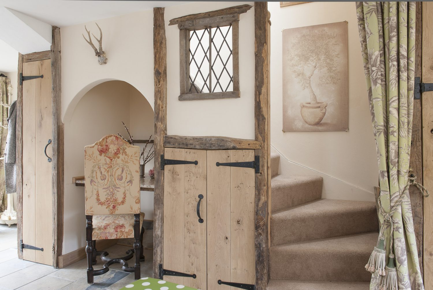 Caroline's 'medieval office wall'.A pink marble-topped desk has been fitted into an arched alcove and a leaded light illuminates the ascent upstairs