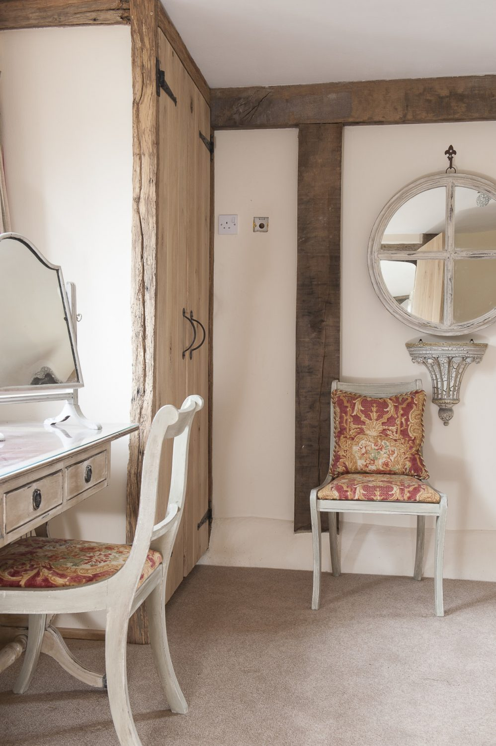 In the main bedroom, two dining chairs have been painted white and covered in Beaumont & Fletcher