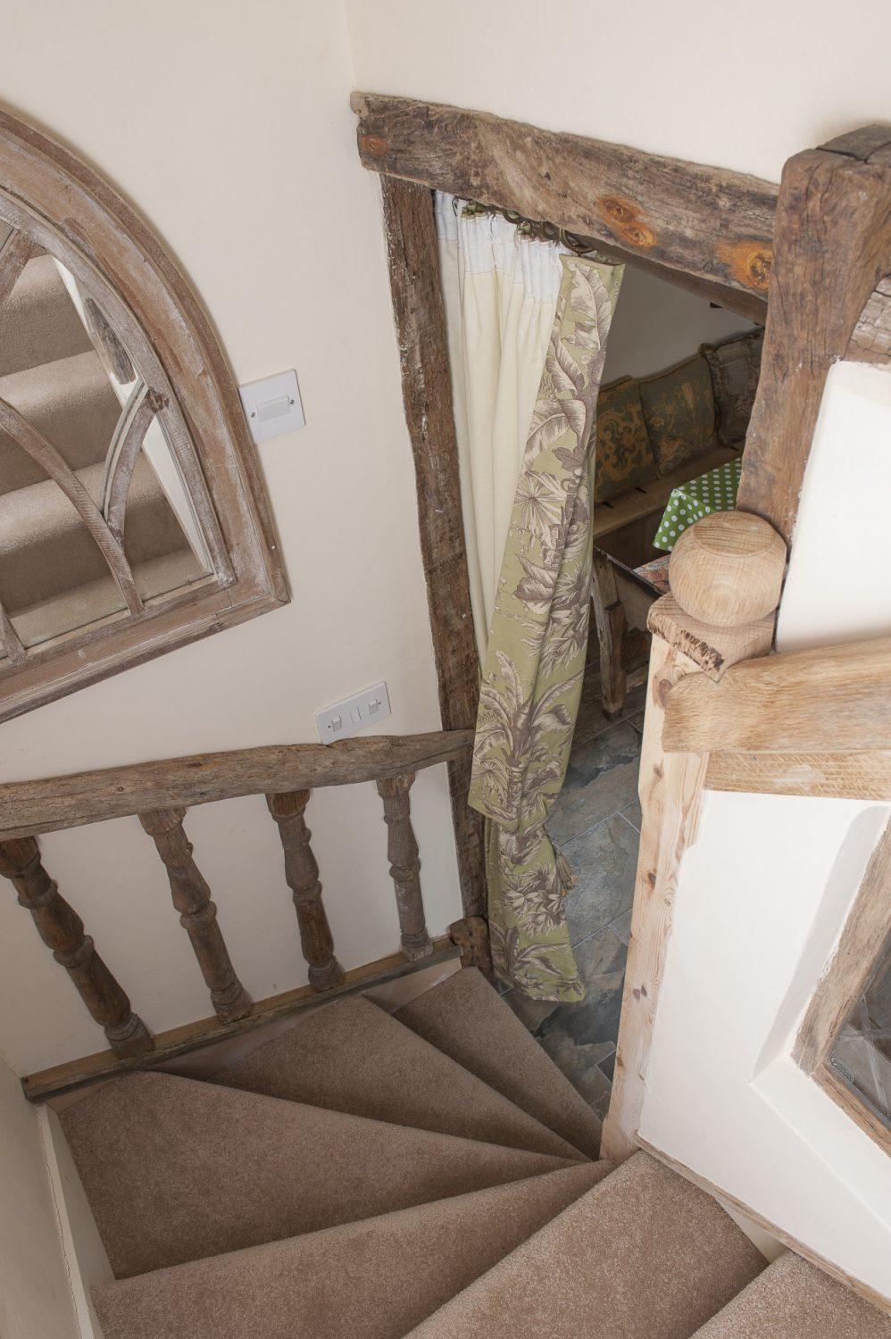 The stairway has been framed in ancient oak whilst oak spindles, left over from the grand reclaimed staircase in Caroline's own barn home, have been set into the wallsThe stairway has been framed in ancient oak whilst oak spindles, left over from the grand reclaimed staircase in Caroline's own barn home, have been set into the walls