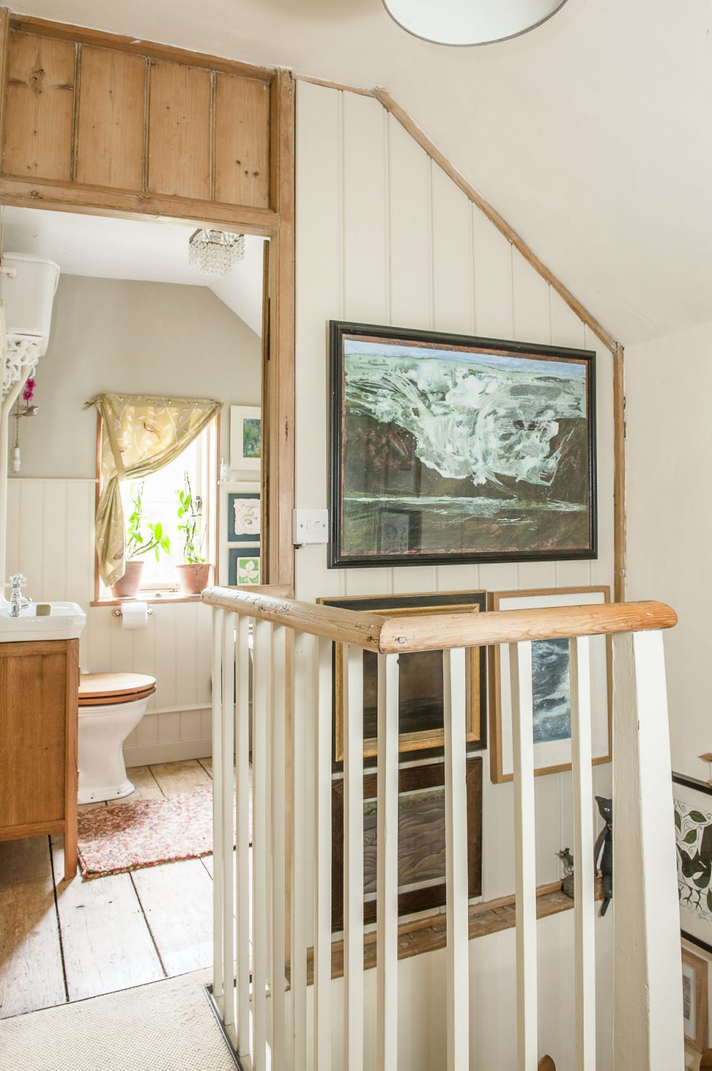 Wendy and Rob have installed two new bathrooms. The walls surrounding the staircase are lined with prints and paintings. At one end of the landing, the first floor bathroom features an elegant roll-top bath