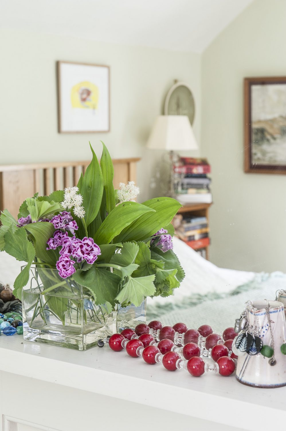 The master bedroom is painted a calming hue of very pale green. As in most rooms of the house, Wendy has gathered flowers and foliage from the garden which are positioned on the mantelpiece alongside her jewellery