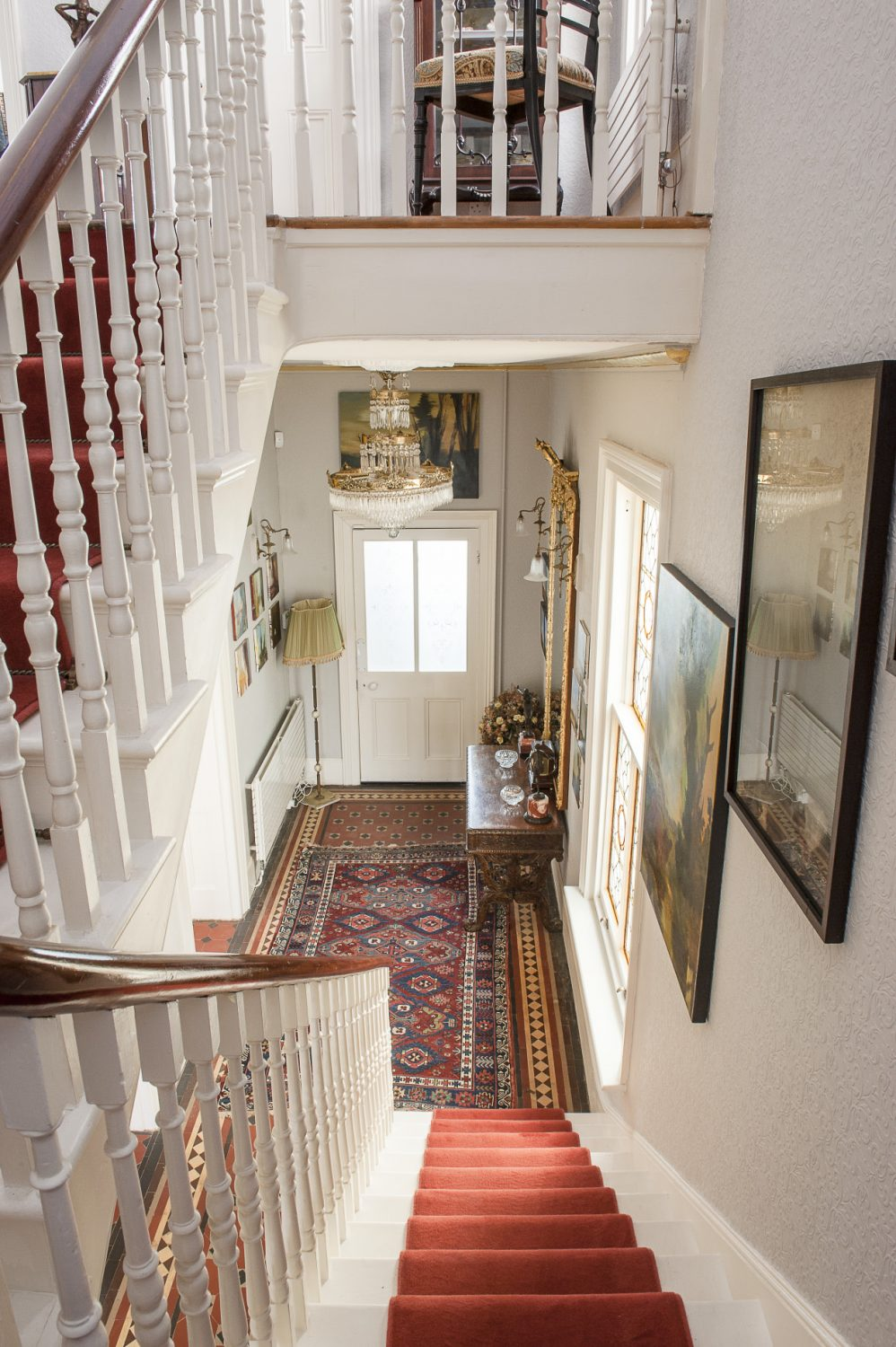 Generously proportioned artworks line the ascent to the first floor and the chandelier-lit hallway including important Rankles