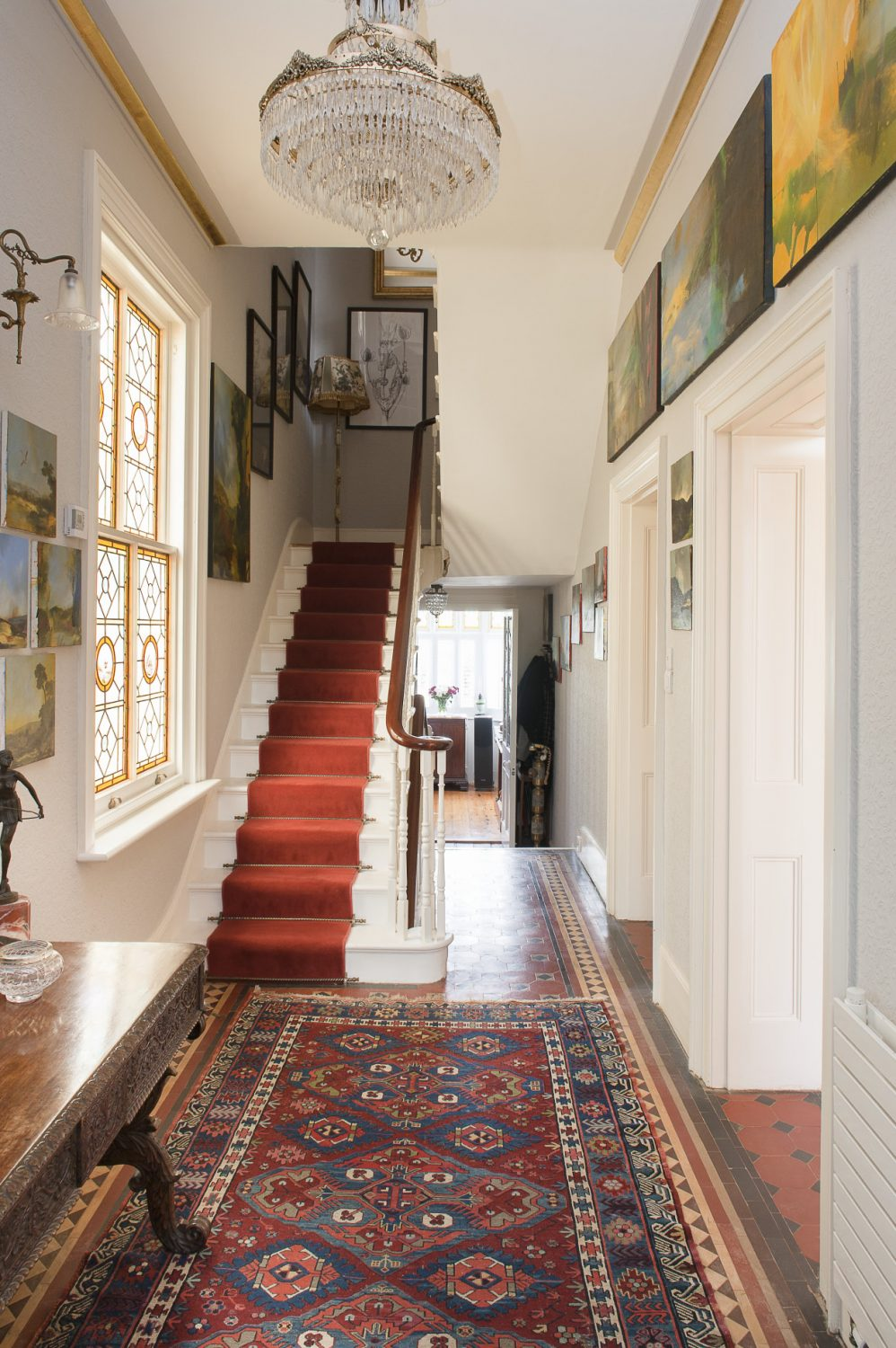 The hallway features a glowing amber stained glass window that Ken sourced in London to replace the original. Doors at the end of the hallway lead into the house's own private chapel