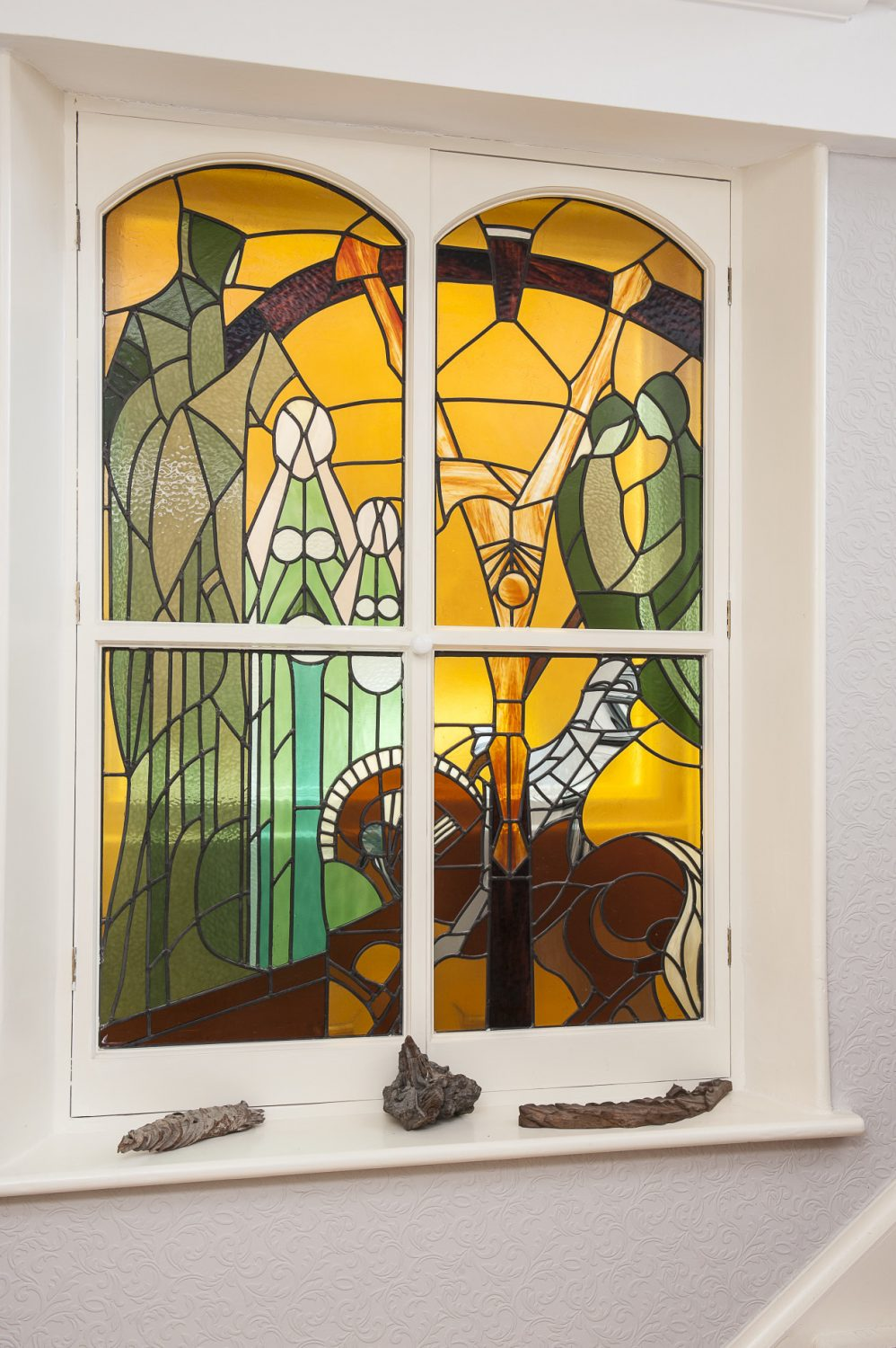 The work of Isobel Ackary is evident in the shape of two lovely stained glass-fronted cabinets and a small basement window