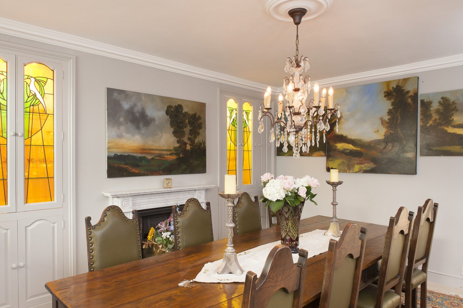 'Below stairs', in what would have been the original kitchen, Ken has created a less formal dining room dominated by a sturdy dark oak dining table from Robert Amstad. On the wall at the head of the table is a stunning Rankle of Calder Valley