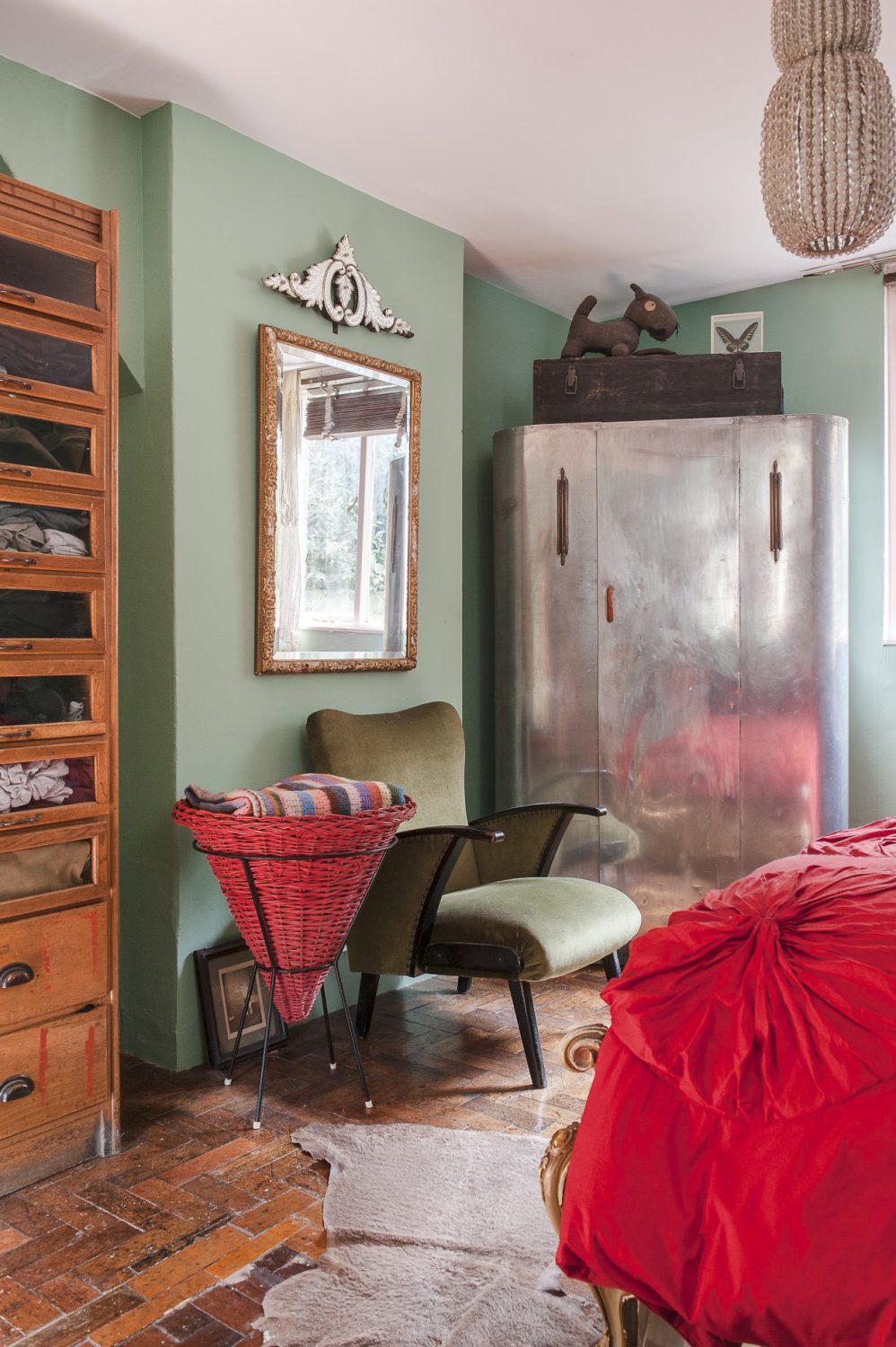 In one corner stands a Deco-style aluminium wardrobe. A toy dog made from an army blanket by Jason's grandfather during the war sits on top. A 1960s conical French laundry basket stands next to an elegant green 1950s armchair