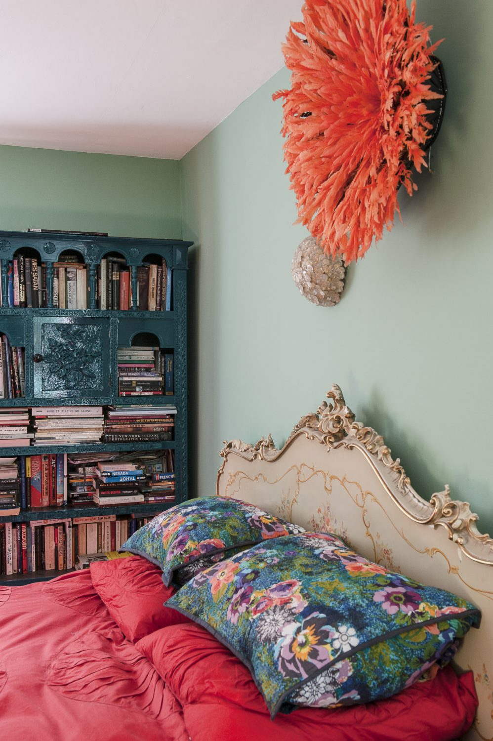 The bedroom features a 1950s Italian gilded bed above which is mounted an orange feathered headdress from the Cameroon