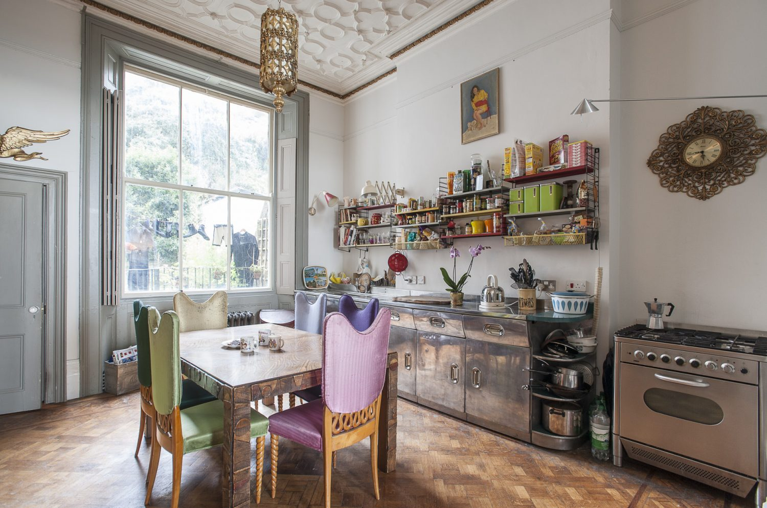 The kitchen gathers around a superb American Brutalist dining table in tiger oak made by US designer Lane above which hangs a tubular and ornate gilt light...