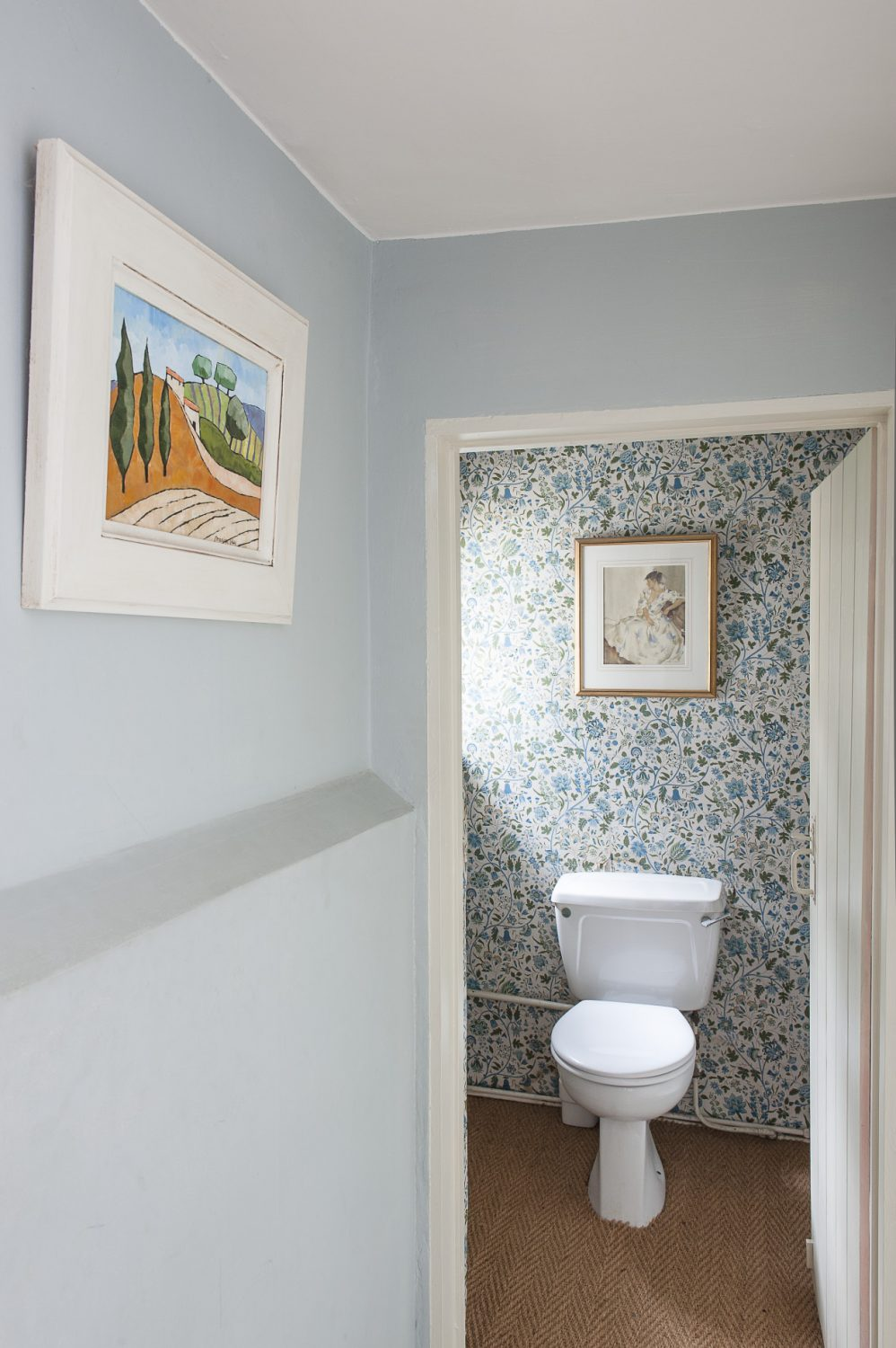 An upstairs loo remains decorated in the original blue floral wallpaper chosen by a previous owner