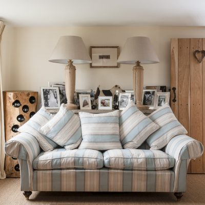 Holly found the elegant blue and white striped sofa at one end of the drawing room from Balmain & Balmain. The lamps and fox terrier toy, interspersed with groupings of family photographs, are from Holly's company Duck & Dog