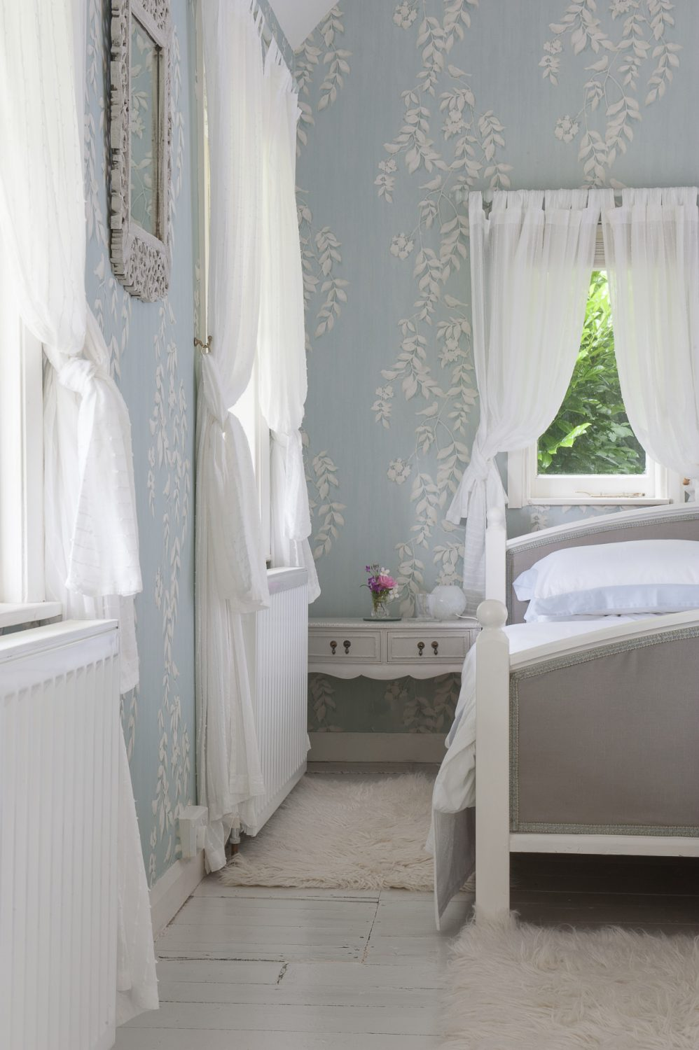 The bedroom is papered in a blue Laura Ashley print. The windows are swathed in romantic cascades of snow-white muslin from Ikea. The couple found the bedroom suite in the Friday Ad