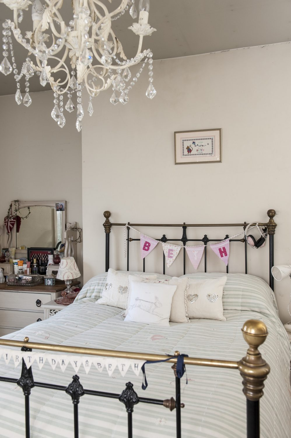 Daughter Beth's room is graced by a brass and iron bedstead and glass chandelier