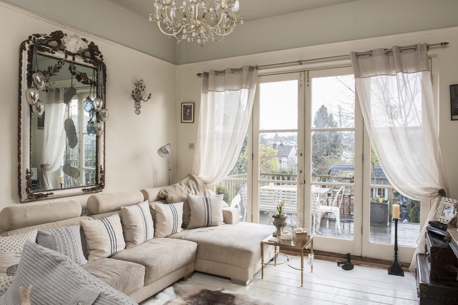 In the more casual area of the drawing room a big cream Danish horseshoe sofa faces the television on the wall opposite and light pours in from a wall of glass doors which open out onto a large timber balcony overlooking the garden