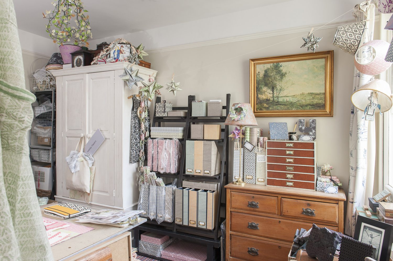 Trudi's workroom shelves are stacked with files in pretty prints, papers and prototypes