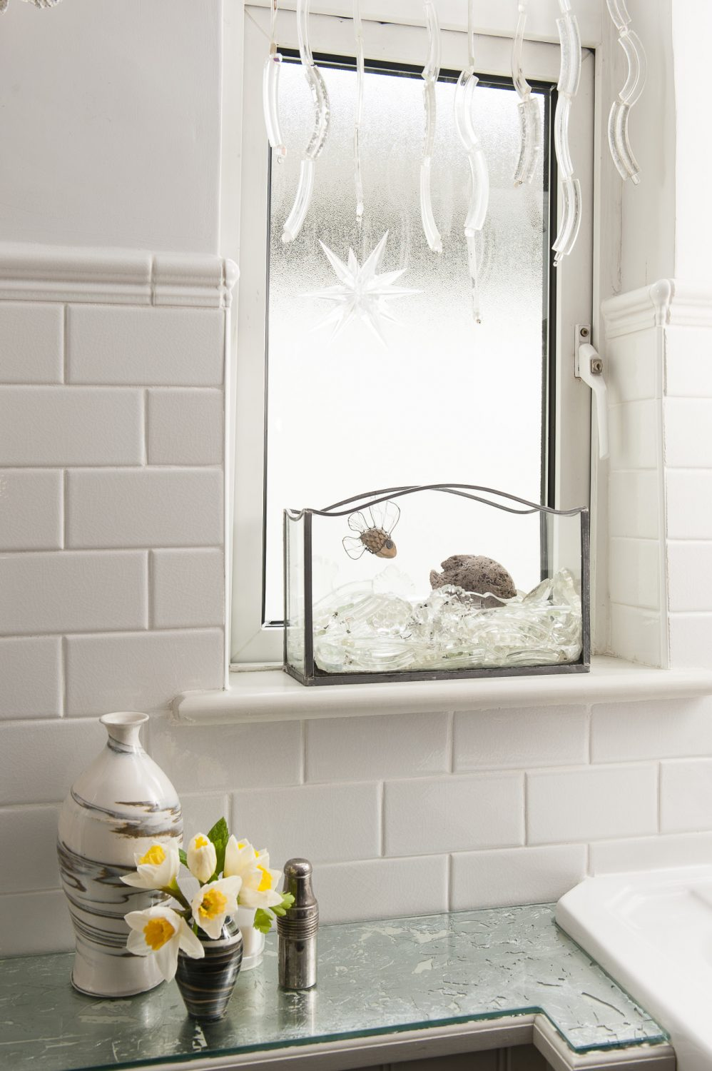 In the bathroom, Trudi has hung glass fragments in the window and created a mock aquarium using salvaged glass, crystal and a little hand-made wire and pebble fish. The off-white tiles are from Fired Earth – a more classic version of Metro tiles, but crackle glazed