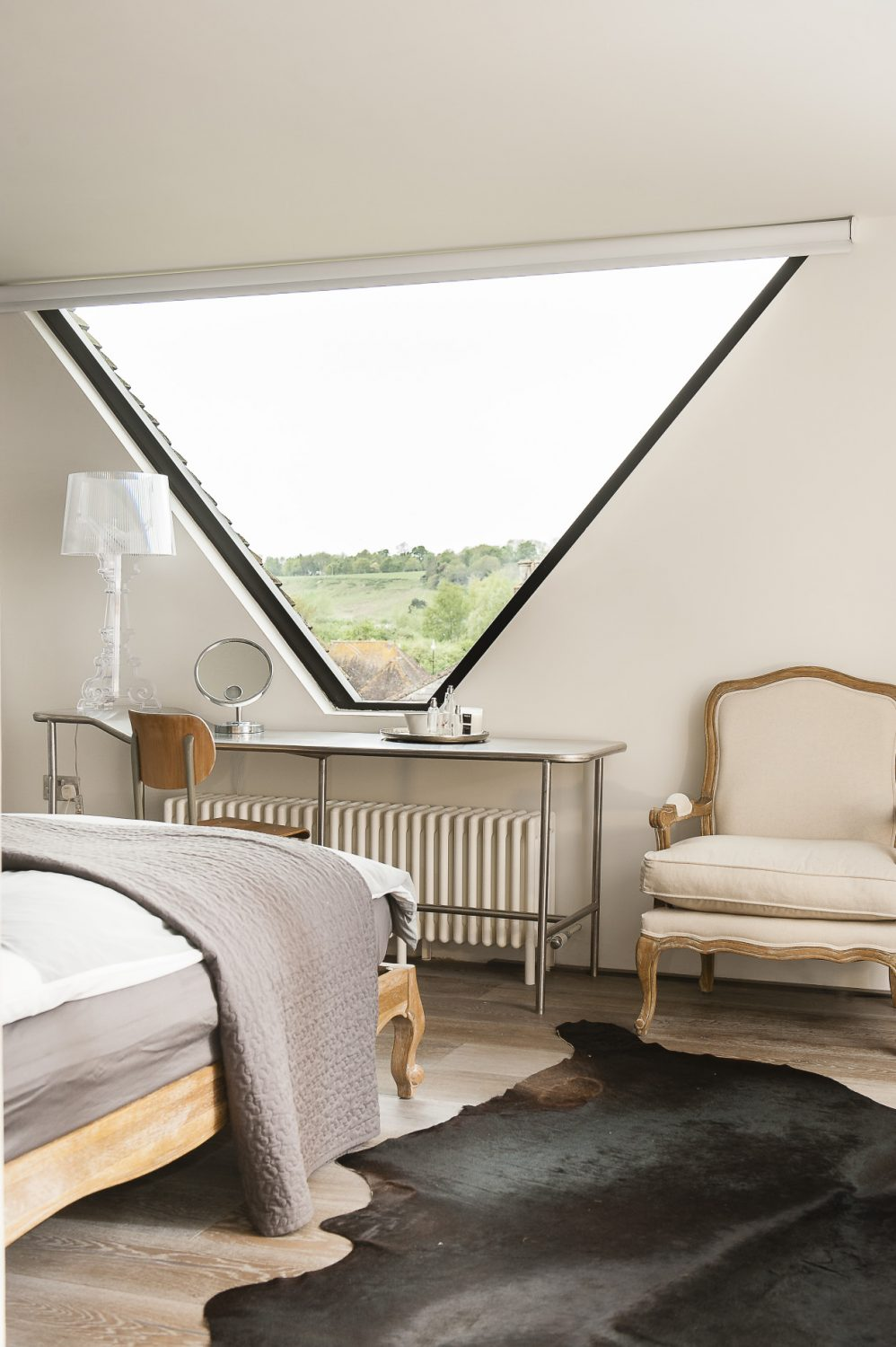 The master bedroom features an amazing triangular window that spans between the twin gables of the roof from which there are wonderful views of the surrounding buildings and the countryside beyond