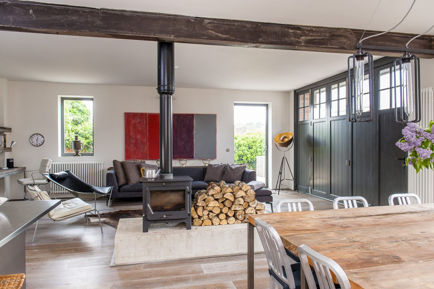 A new set of functional doors have been made in the same style. The double sided wood burning stove and adjacent log pile are housed on a huge concrete plinth, creating a focal point, whether the fire is lit or not