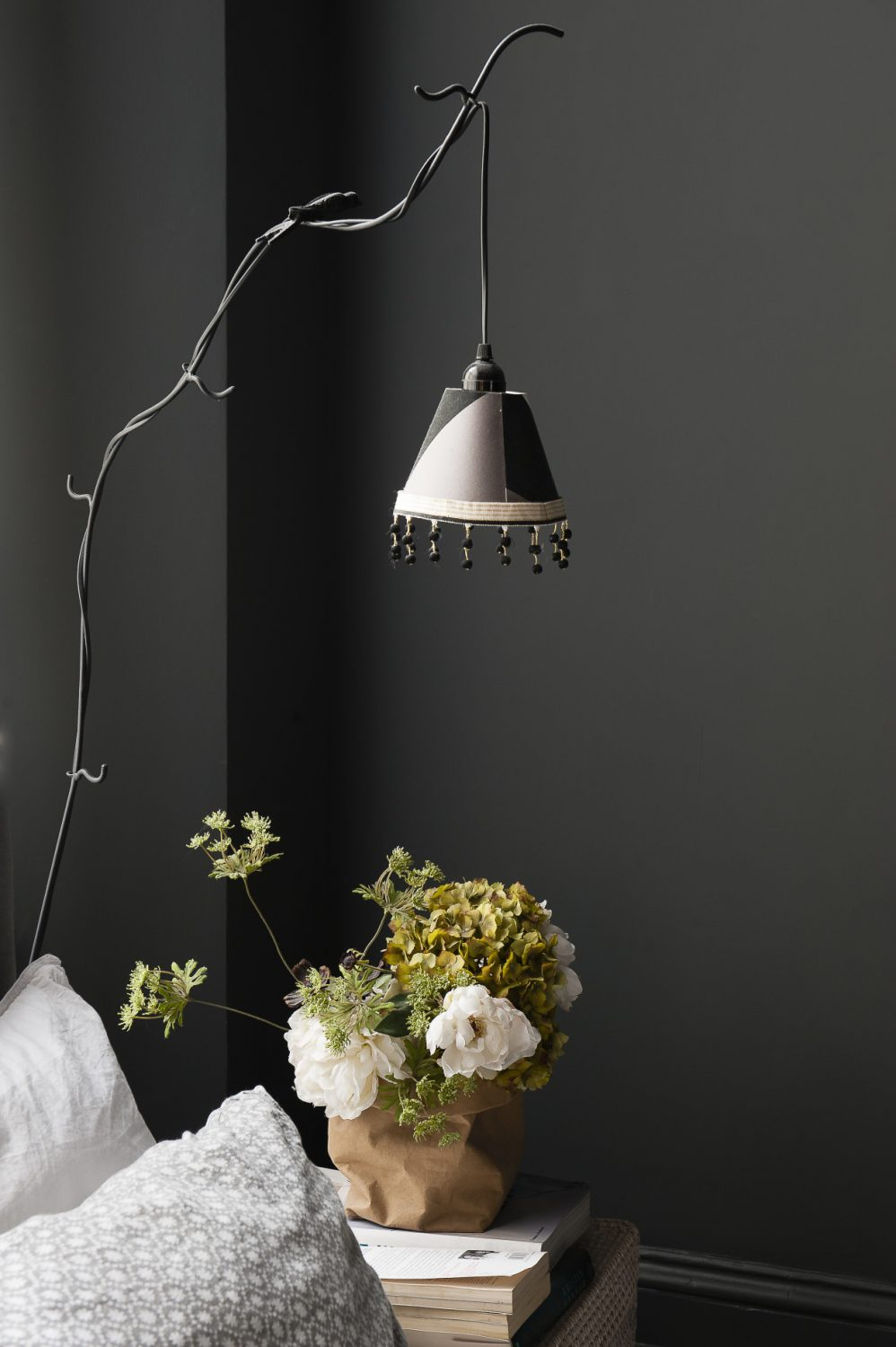 A beautiful twig-like metal floor lamp with a beaded shade acts as a bedside light