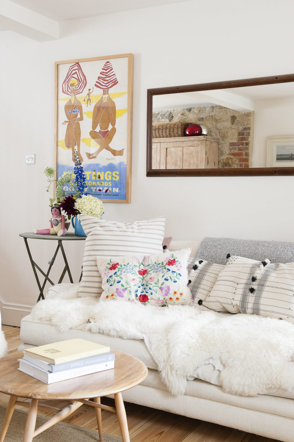 In the main room, the theme of white walls and vintage items in bright and pretty colours creates a space that is both intriguing and tranquil
