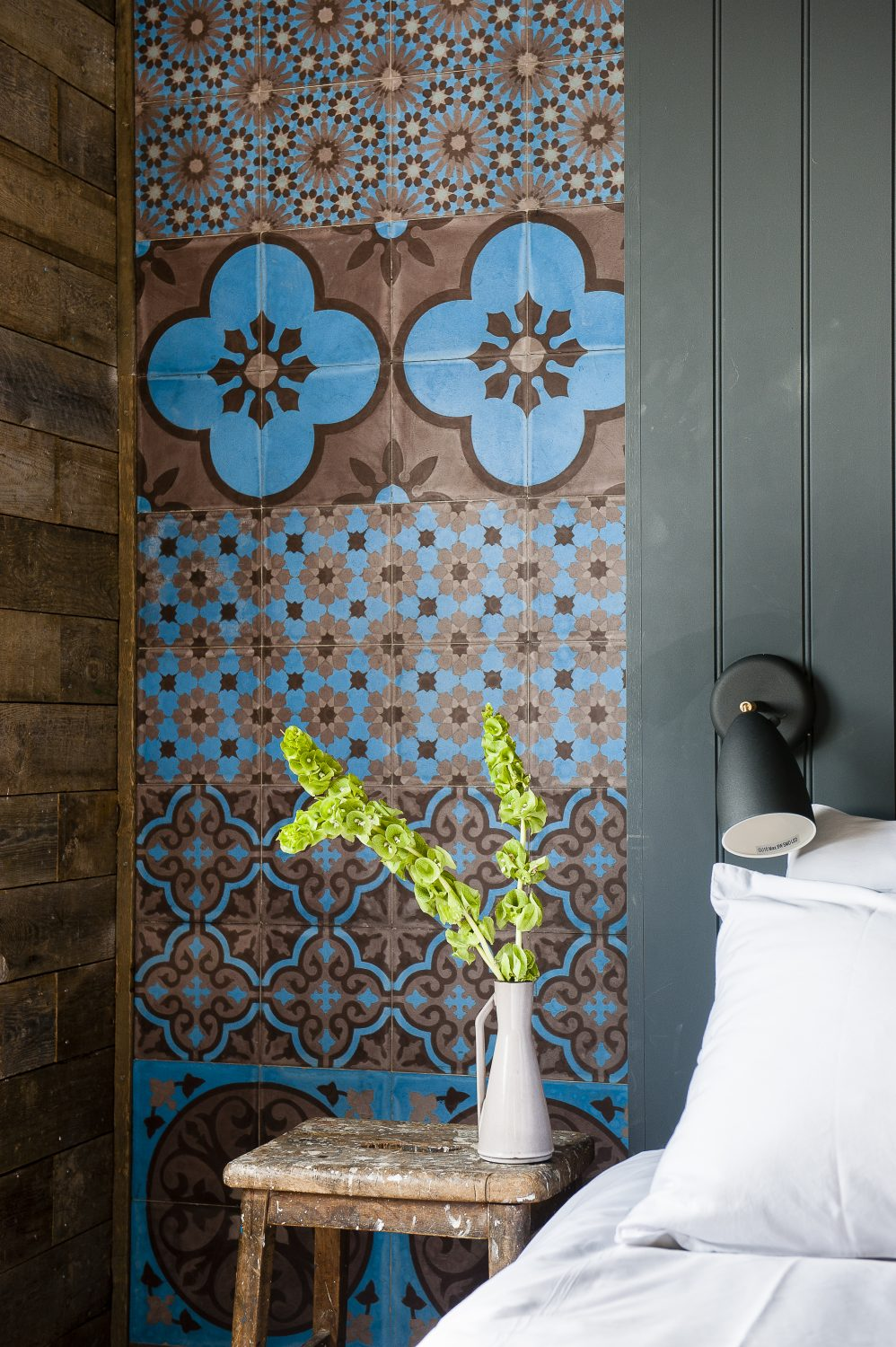 John and Anna built the guest cabin from scratch. Decorative tiles on either side of the bed were sourced by Anna from Emery et Cie in Belgium