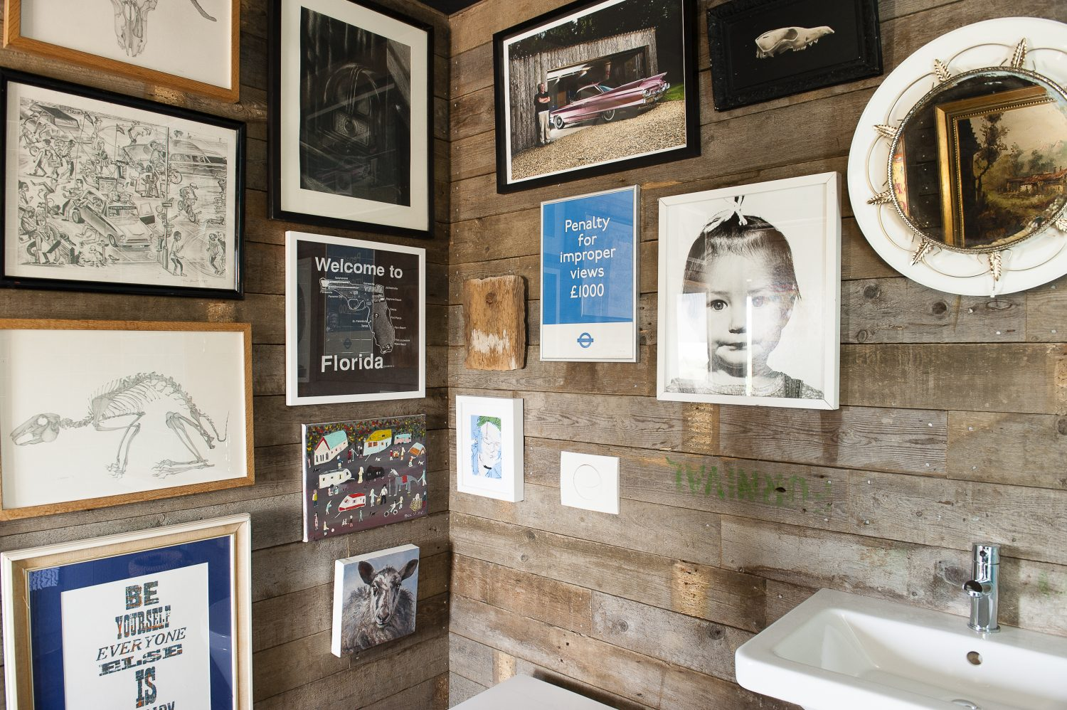 The bathroom walls are lined with an eclectic mix of artworks and photographs