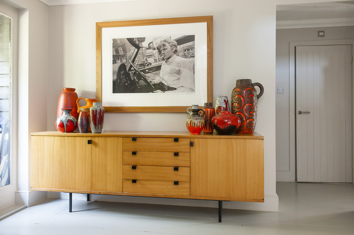 A collection of vintage German pottery in warm shades of orange and red complements the honey-toned sideboard in the hallway downstairs Left: Artwork for Ozzy Osbourne's album No Rest for the Wicked, for which John was Creative Director, is framed in an ornate gilded frame