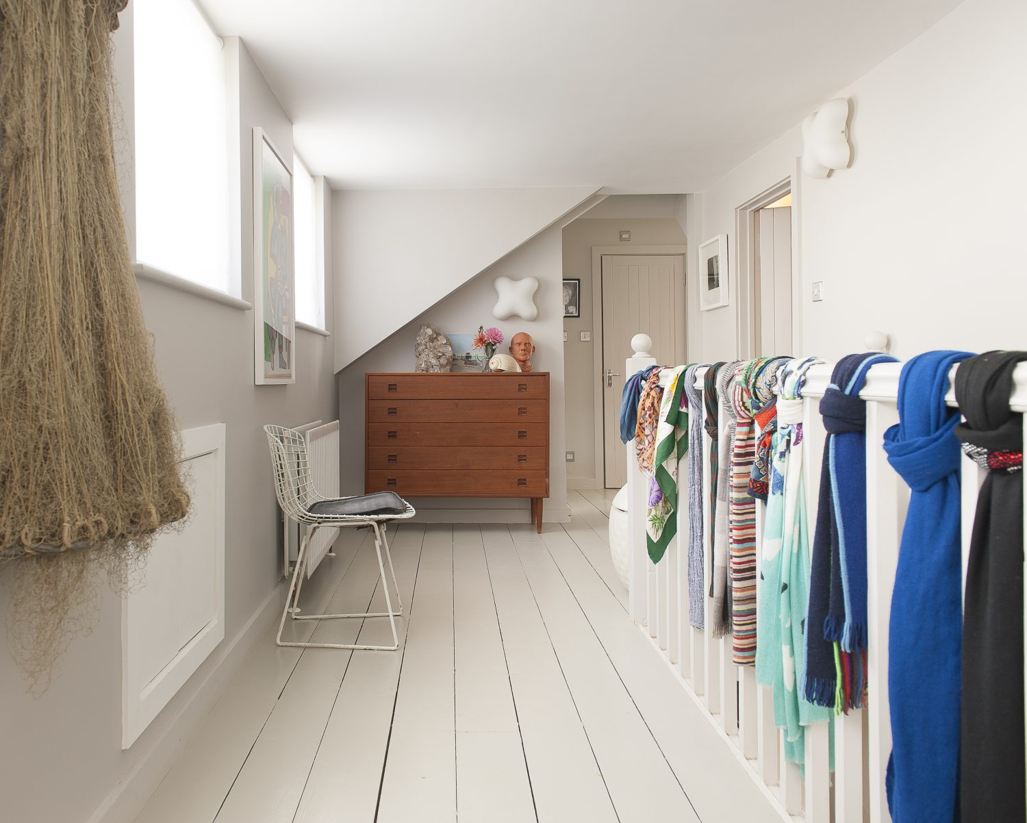The landing. Scarves are tied onto the bannisters, introducing pops of colour to an otherwise neutrally painted space