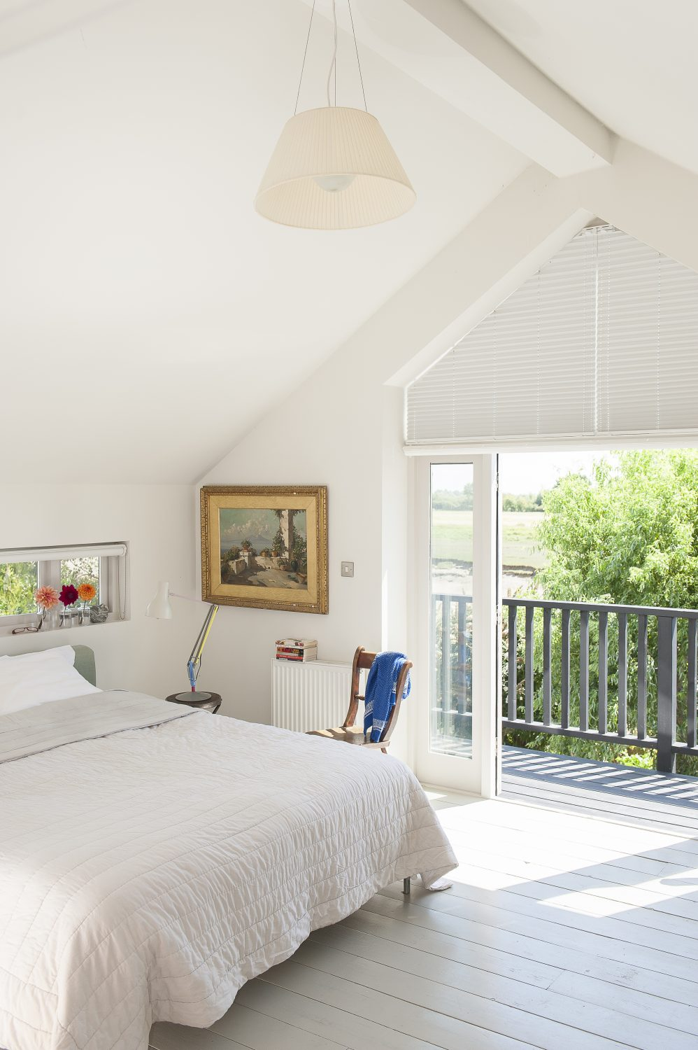 The lofty master bedroom features a balcony which looks out onto the river