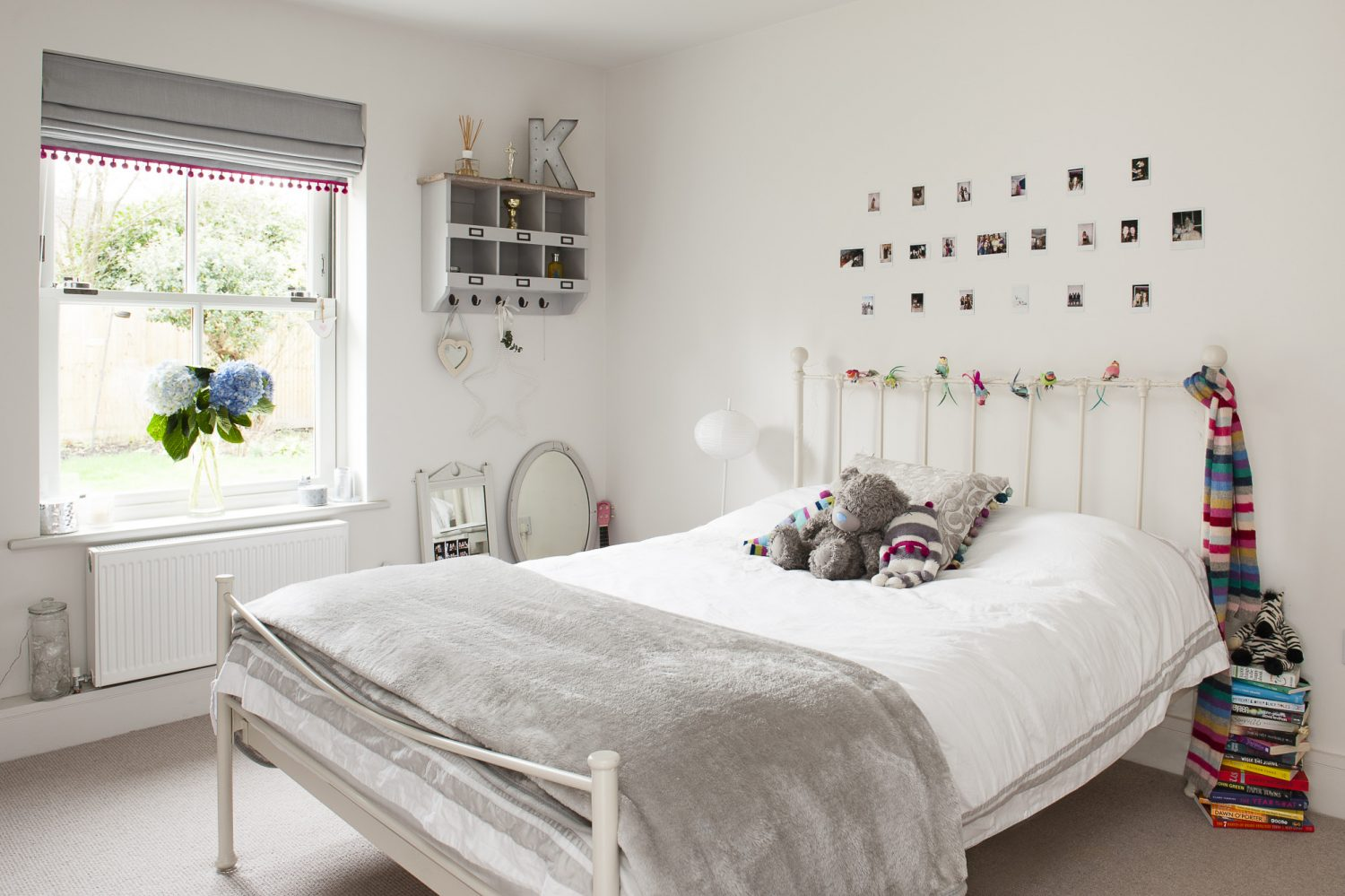 Katie's room is remarkably tidy. The pink pom-pom trim on the blinds is a recent addition that matches her pink chair