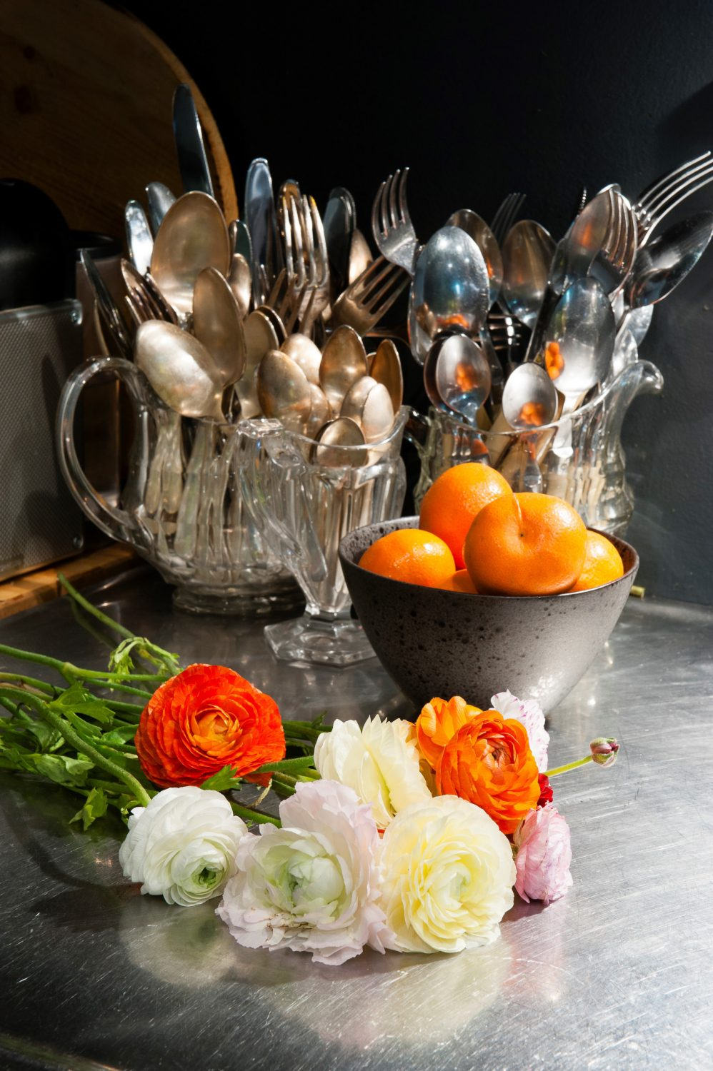 In keeping with the grand, rich feeling of the whole apartment, Karen's cooking utensils and cutlery are kept in a collection of pressed glass jugs and vases