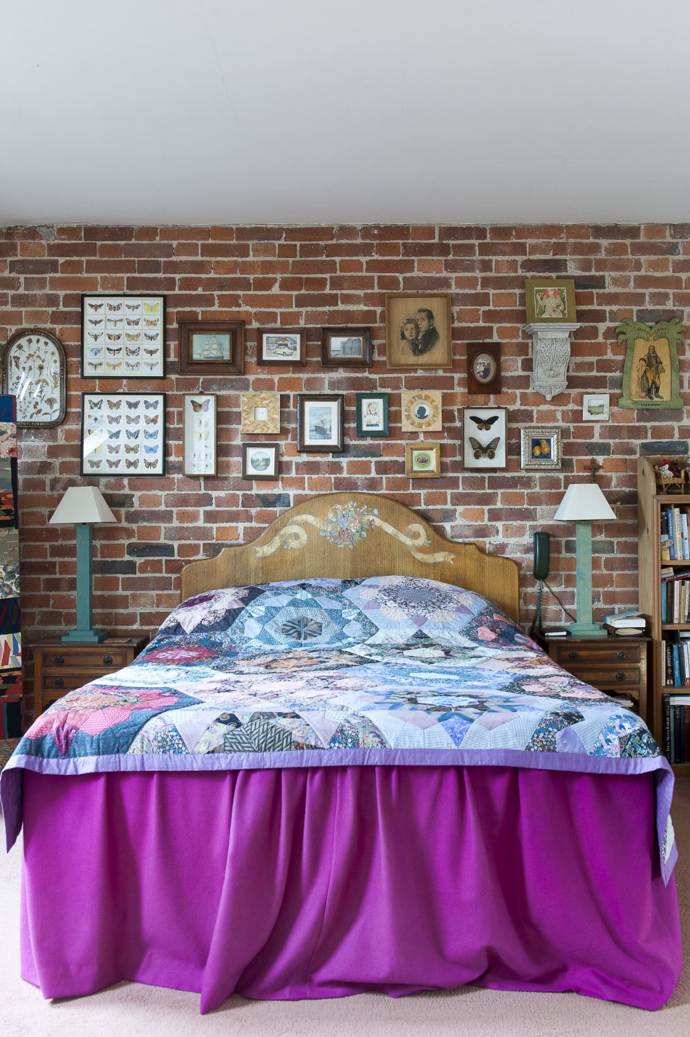 Collections of framed butterflies and portraits line the bare brick wall in the master bedroom. The quilt was handmade locally