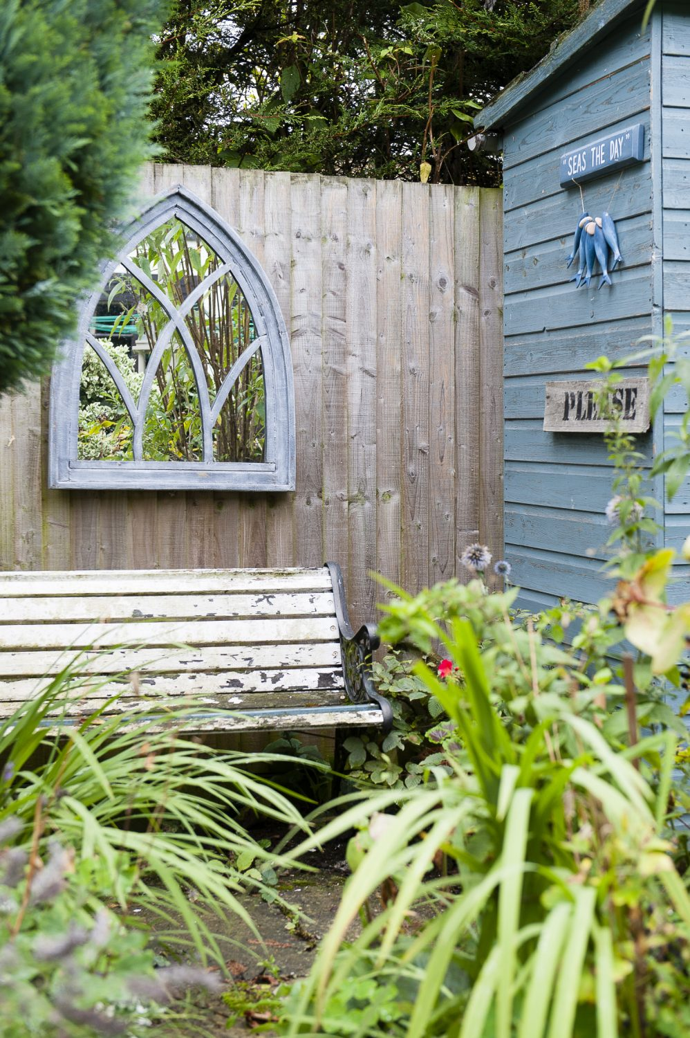 A secluded and tranquil seating area, concealed by borders, can be found at the back of the garden