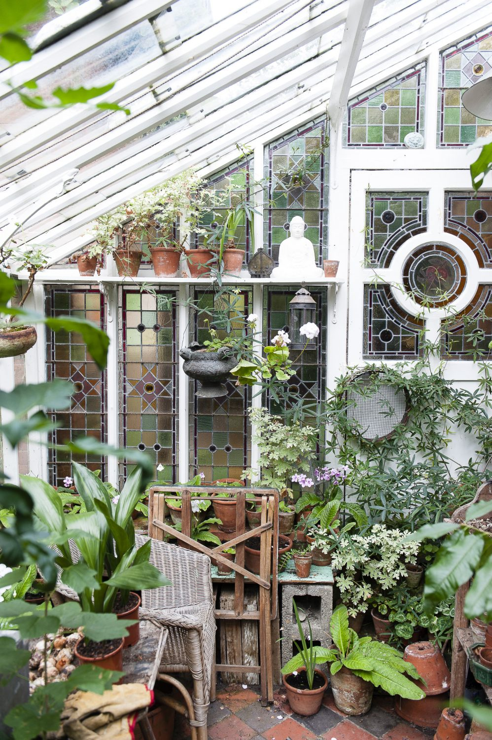 A glasshouse in the garden with stained glass windows