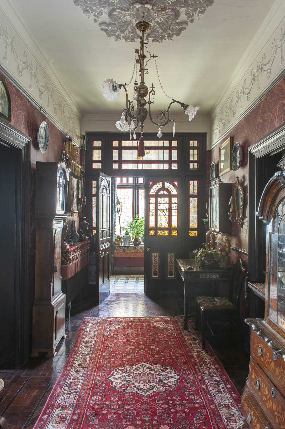 The hall is clearly from another era, every detail in perfect keeping with the late 19th century period of the house, from the rich red wallpaper, polished mahogany furniture and Holophane-shade chandelier, to the taxidermy specimens under glass domes