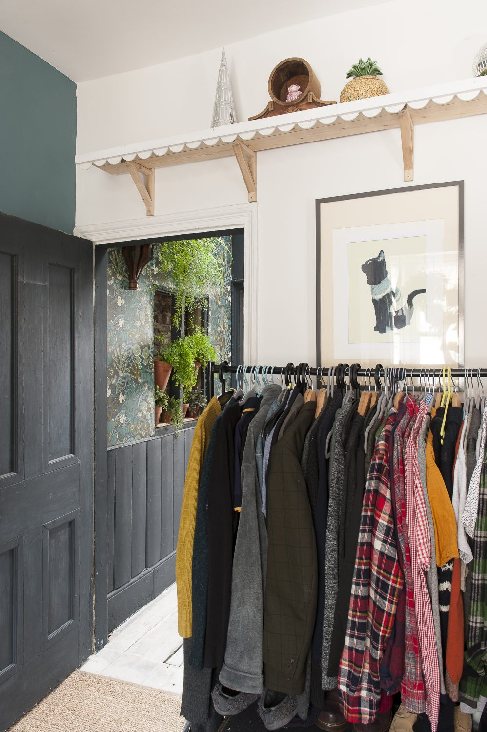 One of the shelves made with a scalloped edge, sits above a rail of clothes
