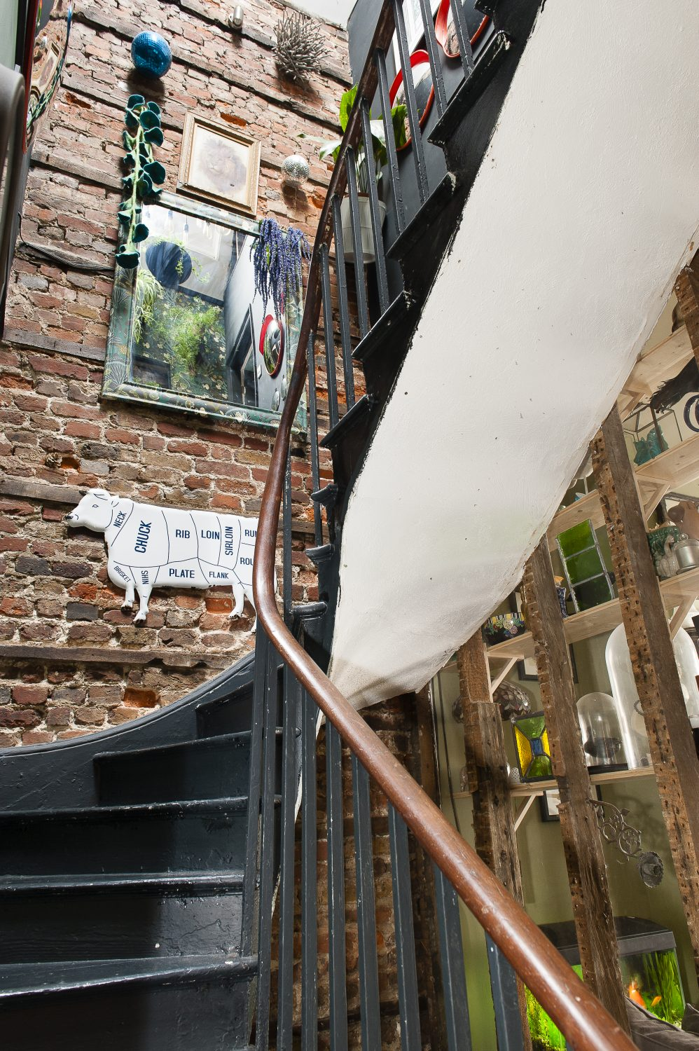 Exposed brickwork cocoons the staircase which rises just behind the shop, going up through the centre of the building. It provides a great backdrop for David and David's paintings and photographs